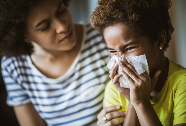 Ill girl blowing her nose at home while her mother is consoling her