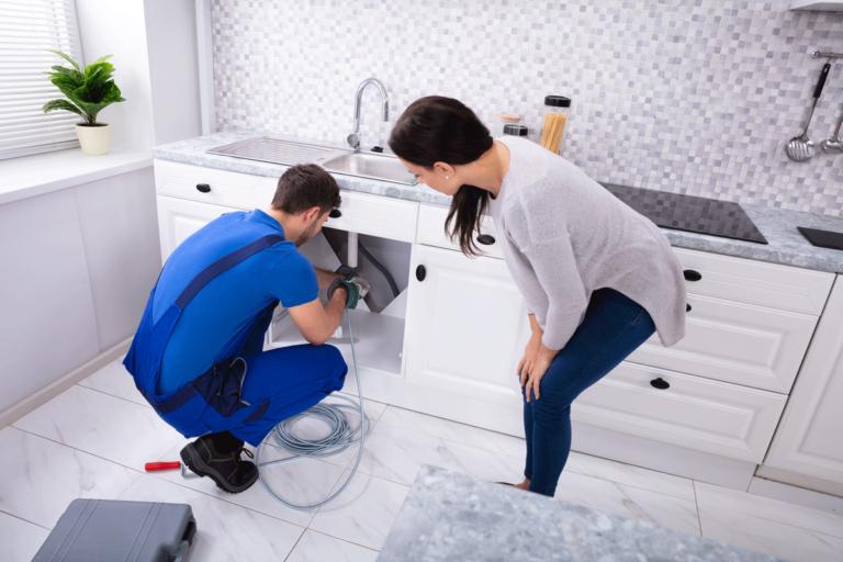 Plumber snaking woman's kitchen sink.
